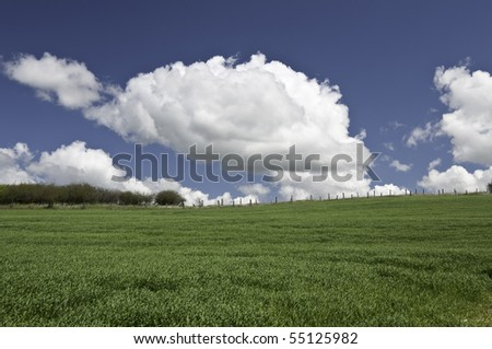 Looking up hill to the fence line and big white clouds above. - stock photo