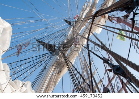 Looking up the tall  mast of a sailboat against blue sky