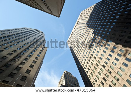 Looking up toward the sky among tall skyscrapers. - stock photo