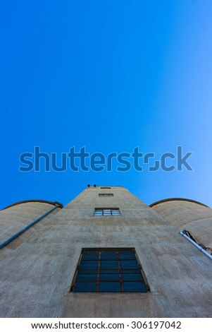 Looking up towards the top of a large silo against blue sky. - stock photo