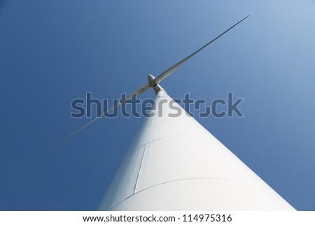Looking upward to a big wind turbine and a blue sky - stock photo