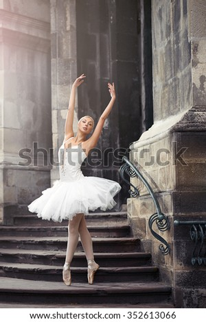 Looks weightless. Beautiful young elegant ballerina dancing on the stairway soft focus - stock photo