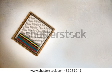 Loom as a souvenir on white wall, isolated. - stock photo