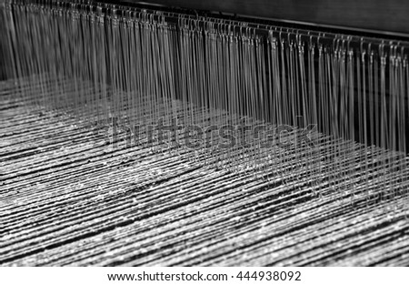 Loom for the production of the fabrics in the ancient textile industry with the black and white color woolen threads for the production of woolen blankets - stock photo