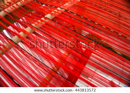 loom strung with red cotton thread ready for weaving cloth - stock photo