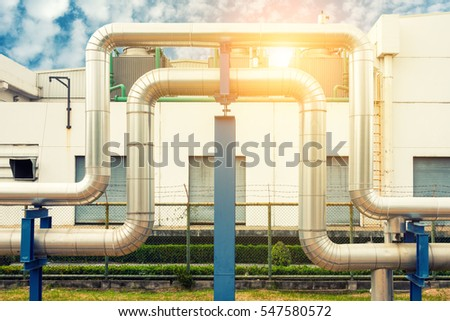 Loop steam pipeline on cooling tower background and sunshine.