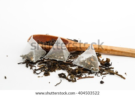loose green tea, tea bags and a wooden spoon on a white background  - stock photo