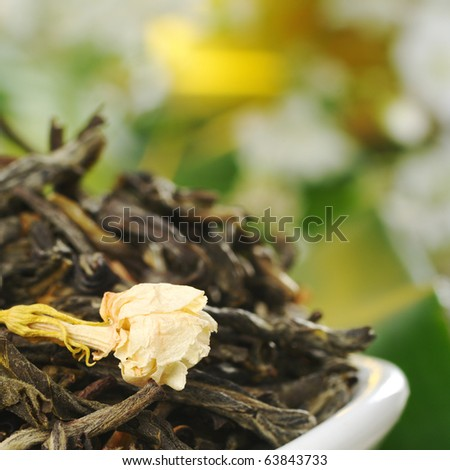 Loose green tea with jasmine flowers with some white flowers in the background (Selective Focus, Focus on the jasmine flower) - stock photo