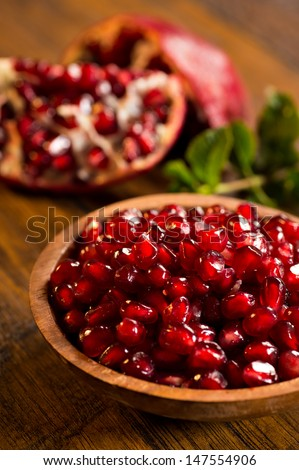 Loose pomegranate (Punica granatum) seeds in a wood bowl shot on a wood table. There are pieces of ripe pomegranate fruit & green mint leaves in the background.  Pomegranates are a super food. - stock photo