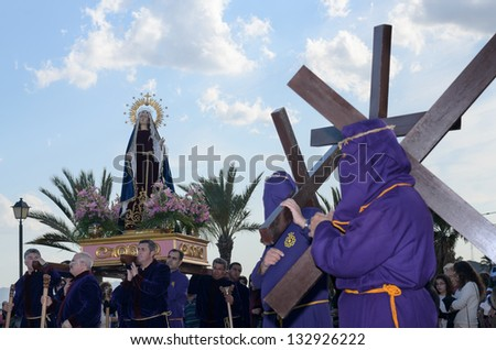 Lorca, Spain - March 22, 2013: Penitential Via Crucis to Calvary with our Lady of Sorrows accompanied with penitents with crosses on his shoulder in Lorca, Spain - stock photo