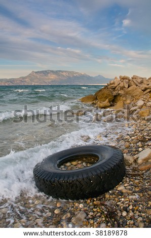 Lorry tyre on sea shore - Pollution - stock photo