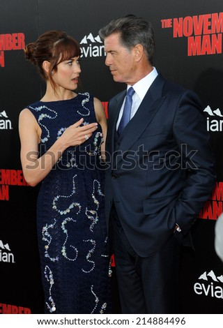 "LOS ANGELES - AUG 13:  Olga Kurylenko & Pierce Brosnan arrives to the ""The November Man"" World Premiere  on August 13, 2014 in Hollywood, CA.                 - stock photo"