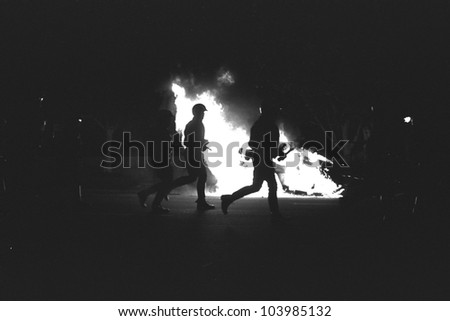 LOS ANGELES, CA - APRIL 29: LAPD officers in riot gear advance past burning police car on night one of the Rodney King Riots on April 29 1992 in Los Angeles, CA. - stock photo