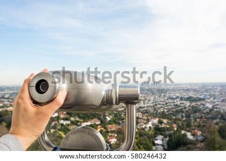 Los Angeles, CA: February 13, 2017:  Hands on a viewfinder at the Griffith Park Observatory.  The Griffith Park Observatory is a popular destination for tourists, with millions visiting each year.
