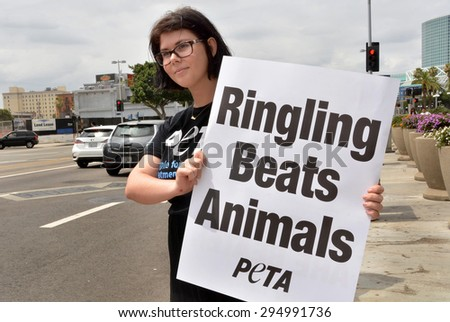 LOS ANGELES, CA â?? JULY 9, 2015: A PETA activist holds a sign toward traffic protesting the treatment of elephants by the Ringling Bros. Circus on July 9, 2015 in Los Angeles, California.