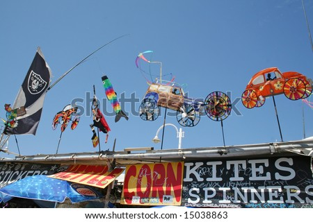 LOS ANGELES, CA - JUNE 15: Colorful Kites and spinners on display above the shop front signs covered with graffiti at Venice Beach In Los Angeles June 15 - 2008. - stock photo