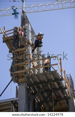 Los Angeles, CA June 20th, 2008:  Construction workers on a building in Los Angeles with a crane in the background.