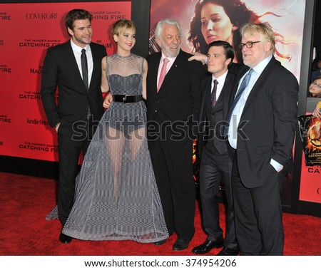 "LOS ANGELES, CA - NOVEMBER 18, 2013: Jennifer Lawrence with Liam Hemsworth (left), Donald Sutherland, Josh Hutcherson & Philip Seymour Hoffman at the premiere of  ""The Hunger Games: Catching Fire"" - stock photo"