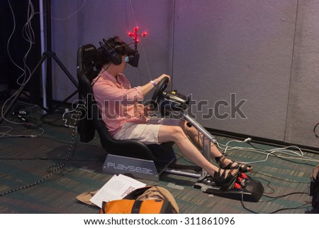 Los Angeles, CA - USA - August 29, 2015: Guy tries virtual glasses headset during VRLA Expo, virtual reality exposition, event at the Los Angeles Convention Center in Los Angeles. - stock photo