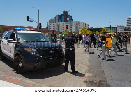 Los Angeles, CA, USA - May 02, 2015: Police watching Protestants during march against the death of Freddie Gray, a man of Baltimore who was seriously injured in police custody. - stock photo