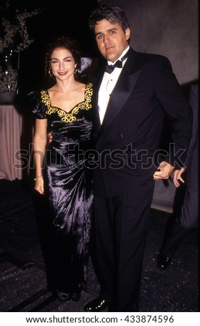 LOS ANGELES, CALIFORNIA - Exact date unknown - circa 1990 - Gloria Estefan and Jay Leno attending a celebrity event - stock photo