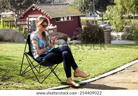 LOS ANGELES, CALIFORNIA, FEBRUARY 16, 2015: Young woman sitting on a foldable chair and texting with her phone in a park. An activity that is becoming more common every day. - stock photo