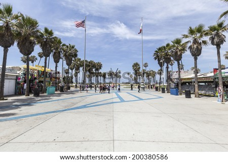 LOS ANGELES, CALIFORNIA - June 20, 2014:  Summer sun and palm trees at the funky Windward plaza at Venice Beach in Los Angeles, California.   - stock photo