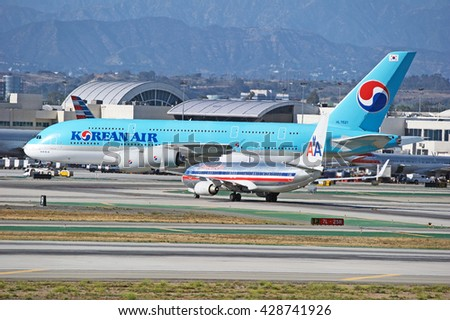 LOS ANGELES/CALIFORNIA - MAY 22, 2016: Korean Air Airbus A380 and and American Airlines Boeing 737 traverse the tarmac at Los Angeles International Airport, Los Angeles, California USA - stock photo