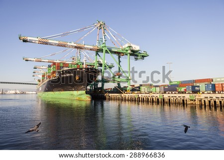 LOS ANGELES, CALIFORNIA, USA - September 25, 2010:  Busy cargo container dock in the congested Los Angeles Harbor.   - stock photo