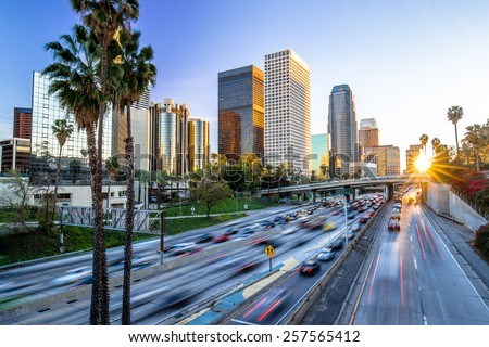 Los Angeles evening sunset highway traffic skyline buildings - stock photo