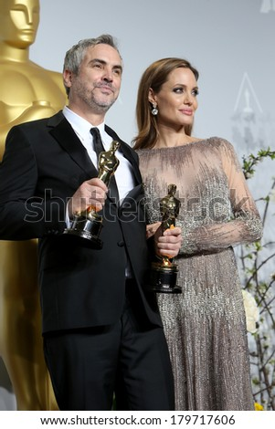 LOS ANGELES - MAR 2:  Alfonso Cuaron, Angelina Jolie at the 86th Academy Awards at Dolby Theater, Hollywood & Highland on March 2, 2014 in Los Angeles, CA - stock photo