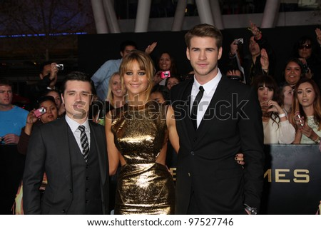 """LOS ANGELES - MAR 12:  Josh Hutcherson; Jennifer Lawrence; Liam Hemsworth arrives at the """"Hunger Games"""" Premiere at the Nokia Theater at LA Live on March 12, 2012 in Los Angeles, CA - stock photo"""