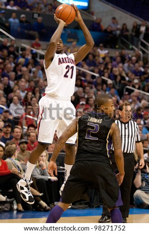 LOS ANGELES - MARCH 12: Arizona Wildcats G Kyle Fogg #21 shoots over Washington Huskies G Isaiah Thomas #2 during the NCAA Pac-10 Tournament championship game on March 12 2011 at Staples Center. - stock photo