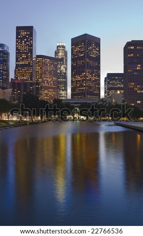 Los Angeles skyline at dusk with buildings reflected in water pool. - stock photo