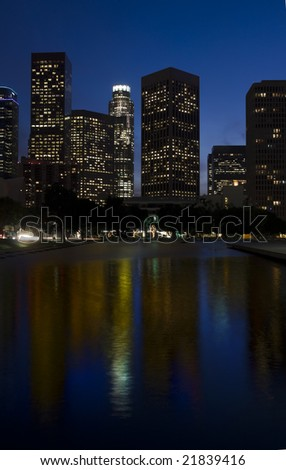 Los Angeles skyline at night with buildings reflected in reflecting pool.