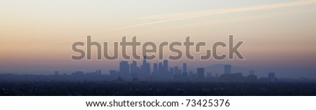 Los Angeles skyline at sunset, showing the large buildings of city downtown with a red sky behind, California, USA - stock photo