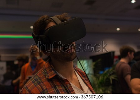 Los Angeles, USA - January 23, 2016: Man tries virtual reality headset  during and hand controls VRLA Expo Winter, virtual reality exposition, at the Los Angeles Convention Center. - stock photo