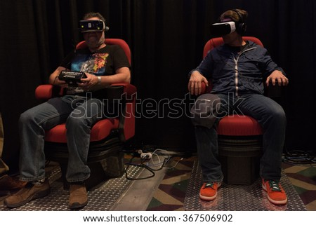 Los Angeles, USA - January 23, 2016: Men tries virtual reality Samsung Gear VR headset during VRLA Expo Winter, virtual reality exposition, at the Los Angeles Convention Center.