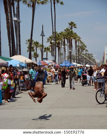 LOS ANGELES, USA - JULY 14, 2013: Acrobat on Venice Beach entertains weekend visitors on July 14, 2013 in Los Angeles.  - stock photo