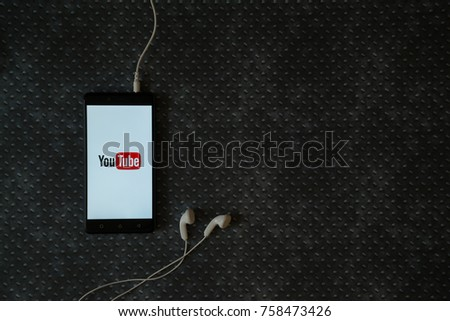 Los Angeles, USA, october 23, 2017: Youtube logo on smartphone screen and earphones plugged in on metal plate background.