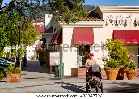 LOS GATOS,CA- Apr 28,2014: Upscale shops in the Old Town business district. A woman with a baby stroller crosses the street. The wealthy Silicon Valley town is the headquarters for tech giant Netflix. - stock photo