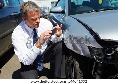 Loss Adjuster Inspecting Car Involved In Accident - stock photo