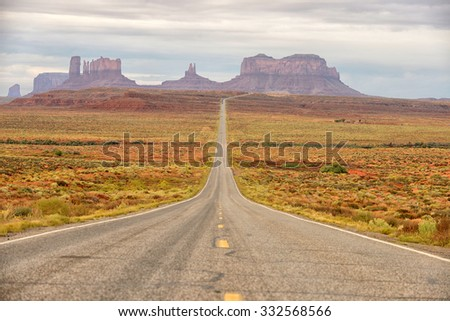 lost and alone on a famous empty road in the middle of nowhere in monument valley - stock photo