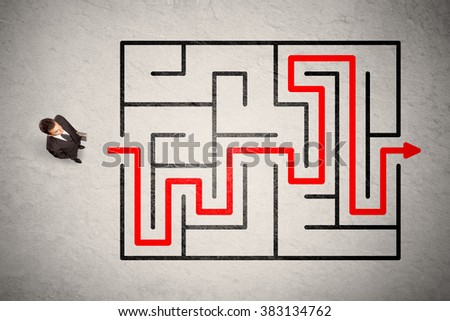 Lost businessman found the way in maze with red arrow on grungy background - stock photo