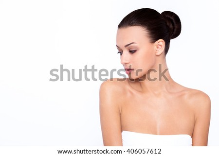 Lost in relaxation. Beautiful young woman stands with his back to the camera and holding hand on the shoulder against white background