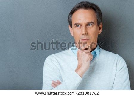 Lost in thoughts. Portrait of thoughtful mature man holding hand on chin and looking away while standing against grey background - stock photo
