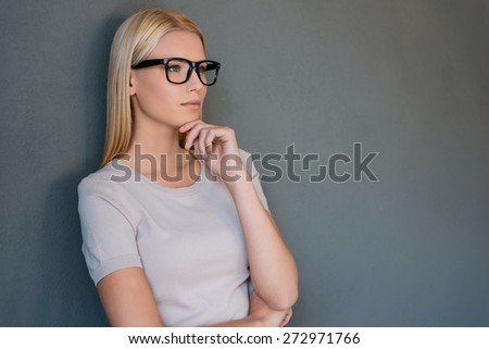 Lost in thoughts. Thoughtful young blond hair woman holding hand on chin and looking away while standing against grey background - stock photo