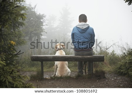 Lost man with his dog in mountain. - stock photo