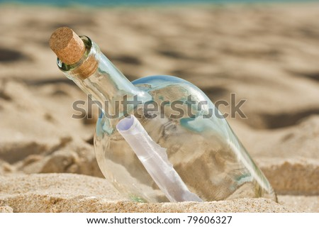 Lost message inside a bottle ashored at the beach and is waiting for someone to find it - stock photo