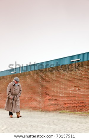 Lost senior man with raincoat and hat walking on empty road on cloudy day. - stock photo